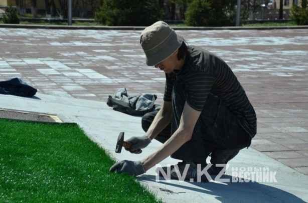 Рабочий прибивает траву нк цветнику мемориала
